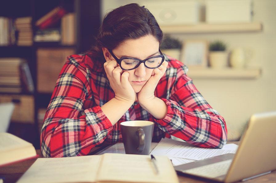 Mulher sentada e sonolenta com xícara de café e notebook na mesa