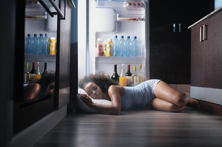 Mulher se refrescando na geladeira para conseguir dormir melhor no calor