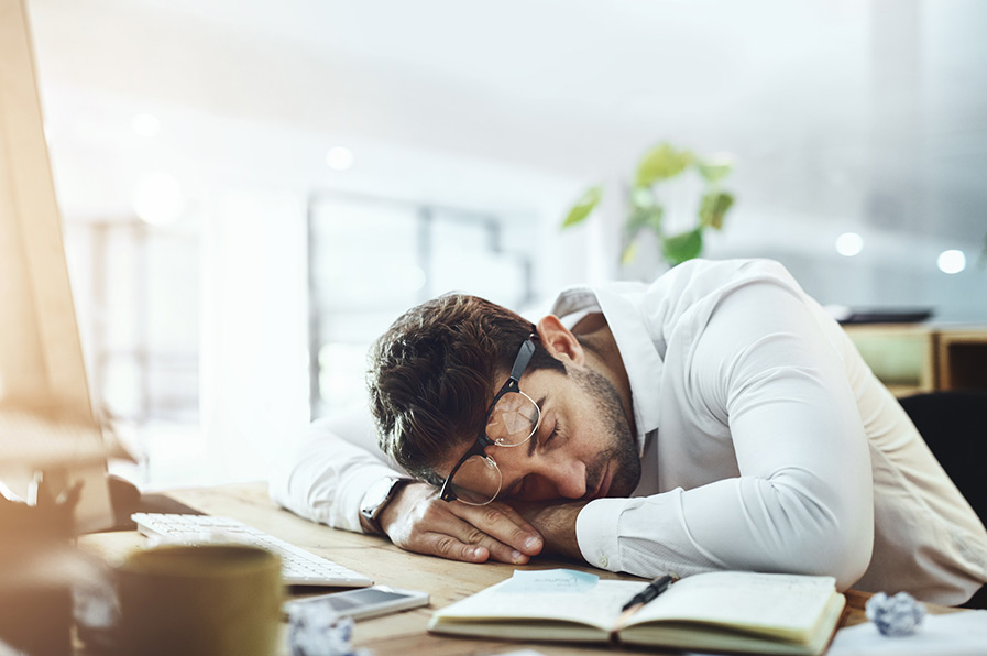 Homem deitado na mesa de trabalho