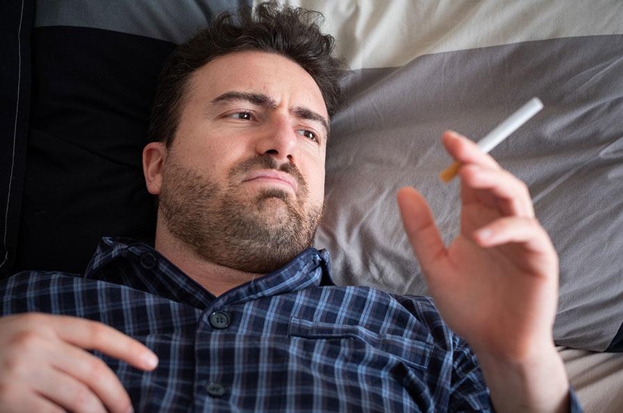 Homem deitado, fumando na cama